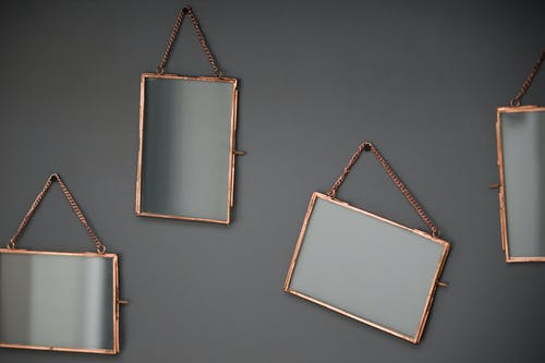 Various modern mirrors with decorative frames and reflection hanging on golden chain in light room on gray background in studio