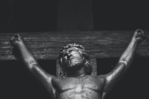Black and white religious aged statue of Jesus Christ crucified on shabby wooden cross located in church against black wall