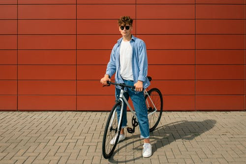 Man in White Dress Shirt and Blue Denim Jeans Riding on Blue Bicycle