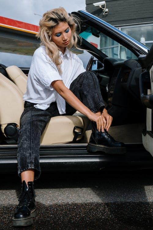 Женщина в белой рубашке и черных джинсах сидит на бежевом автокресле