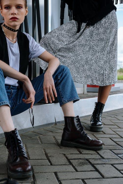 Женщина в серой рубашке и синих джинсах в черных кожаных сапогах