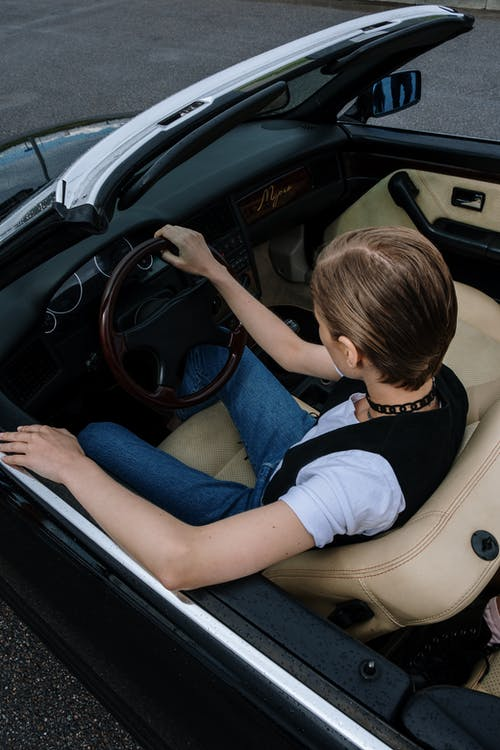 Woman in White T-shirt Driving Car