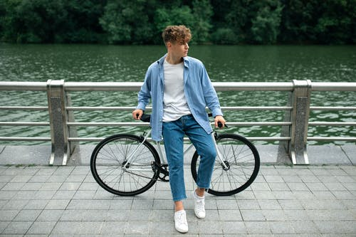 Man in White Dress Shirt and Blue Denim Jeans Standing Beside Black Bicycle