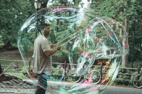 Side view of adult Indian male with sticks standing inside of transparent soap bubble and looking forward in town
