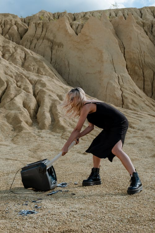 Woman in Black Tank Top and Black Shorts Carrying Black Leather Handbag