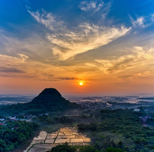 Rice plantations located near mountain under sundown sky in tropical countryside