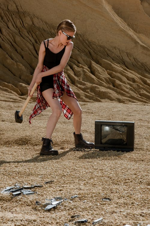 Woman in Black Tank Top and Red Shorts Standing on Brown Sand