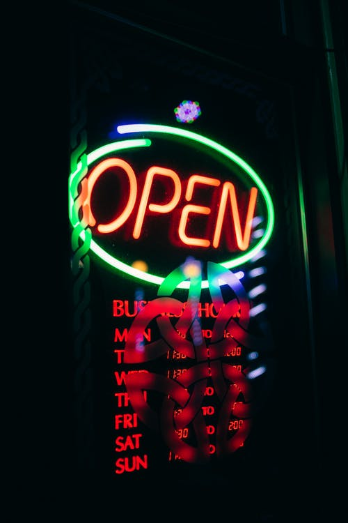 Glowing neon signboard with inscription open on glass door of modern nightclub in late evening