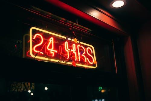 Bright luminous rectangular shaped signboard with inscription 24 hrs on window of nightclub