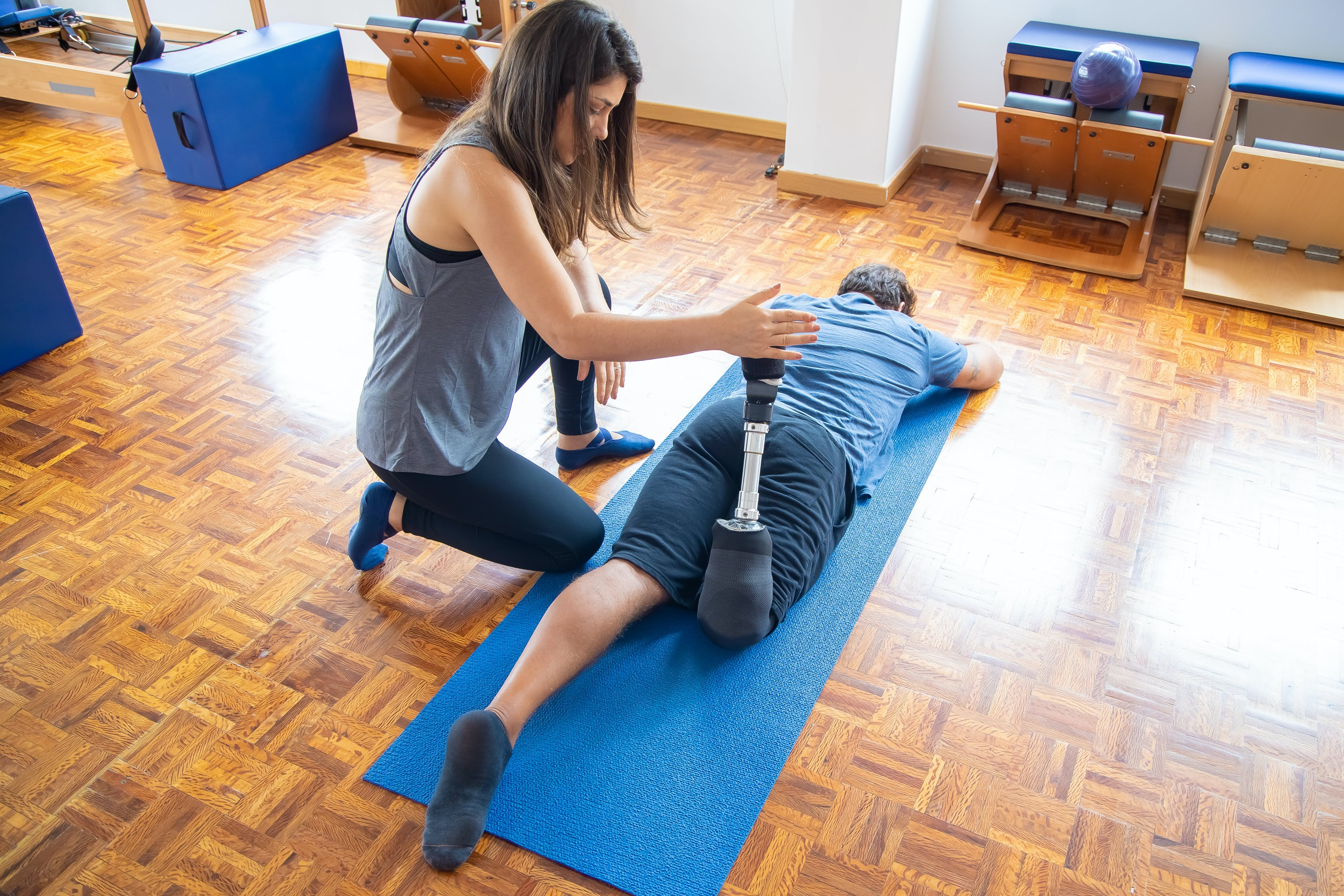 Woman in White Tank Top and Blue Denim Jeans Sitting on Blue Yoga Mat