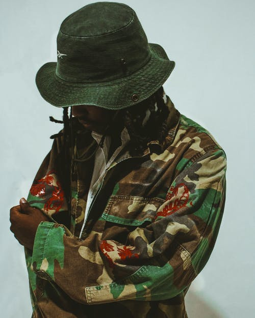 Man in Green and Brown Camouflage Jacket Wearing Black Fedora Hat