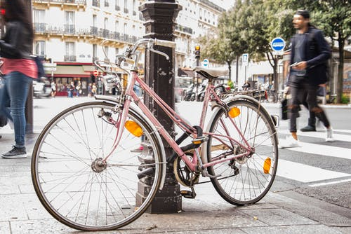 Pink City Bike Leaning on Black Post