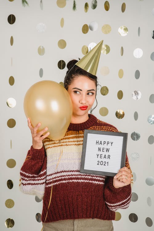 Content female wearing party hat standing on decorated white background with balloon and greeting inscription in hand while celebrating new year
