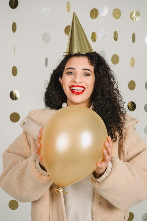 Positive female with dark hair wearing golden party hat looking at camera while standing with balloon in hands on white background with hanging decor