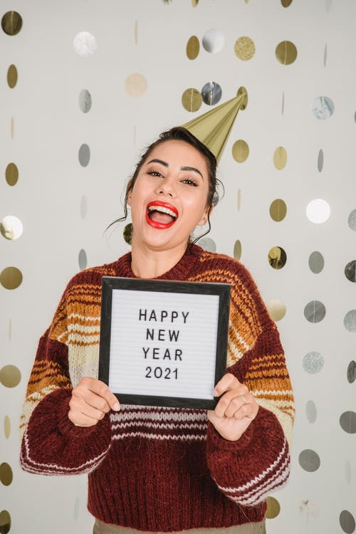 Happy female wearing party hat and warm sweater looking at camera while standing with holiday inscription on tablet against white background with garland