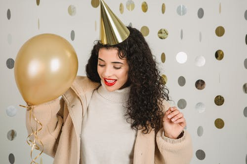 Positive woman with balloon celebrating holiday