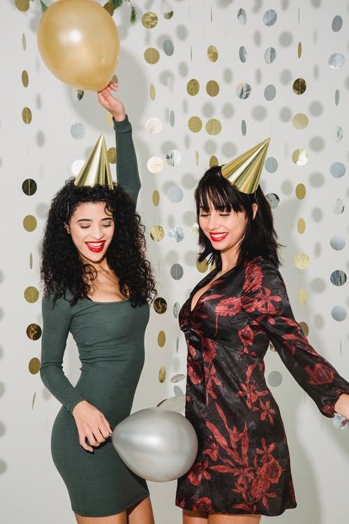 Happy female friends with helium balloons wearing party hats having fun while standing on white background with paper garland during holiday celebration