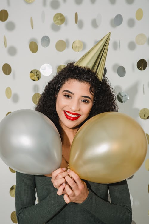 Cheerful female with dark hair wearing party hat looking at camera while standing with colorful balloons on white background with hanging decoration