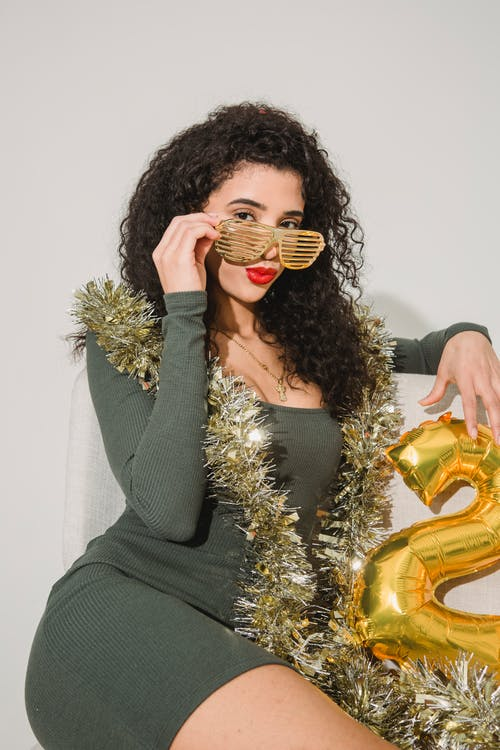 Woman in striped glasses and shimmering tinsel