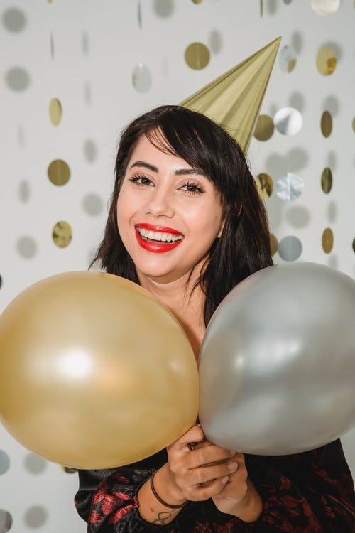 Cheerful woman in birthday cap with silver and golden balloons