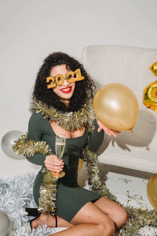 Happy woman in festive glasses and tinsel smiling