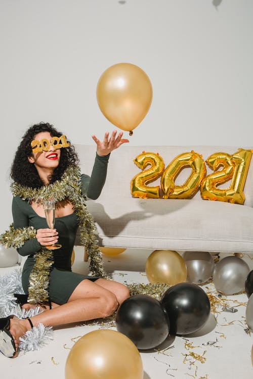 Woman in Brown and Black Leopard Print Coat Sitting on Black and Yellow Balloons