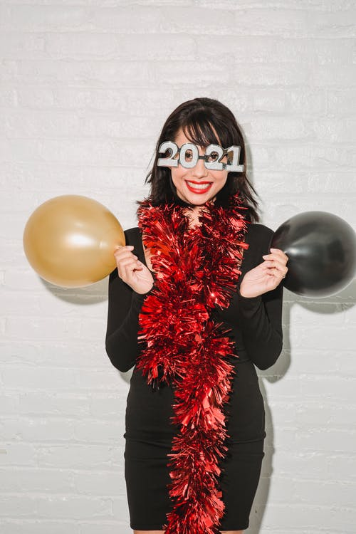 Positive woman in festive glasses and tinsel with balloons
