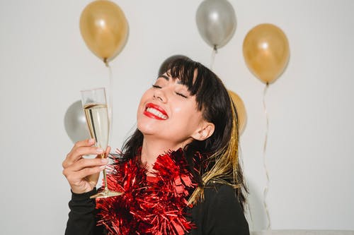 Cheerful young female with closed eyes in tinsel among silver and golden balloons at special event