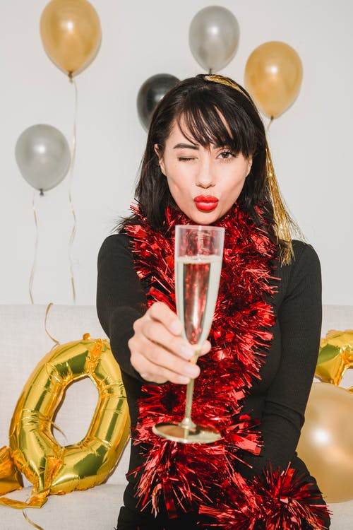 Content woman winking and showing glass of champagne