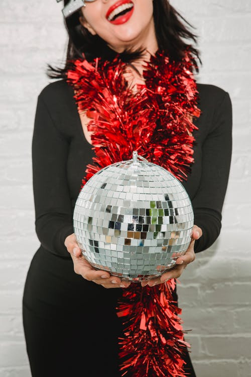 Happy woman in tinsel with mirror ball