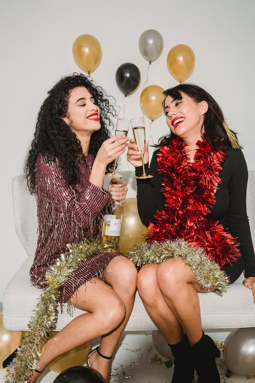 Happy women in sparkling tinsel clinking with glasses of champagne