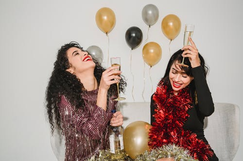 Happy smiling friends with bright red lips and glasses of crystal champagne and red sparkling tinsel celebrating New Year
