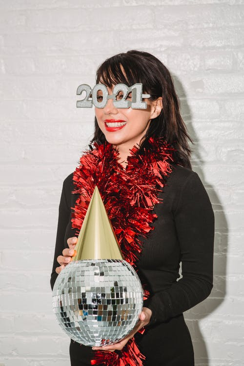 Glad woman in decorative New Year eyeglasses with disco ball