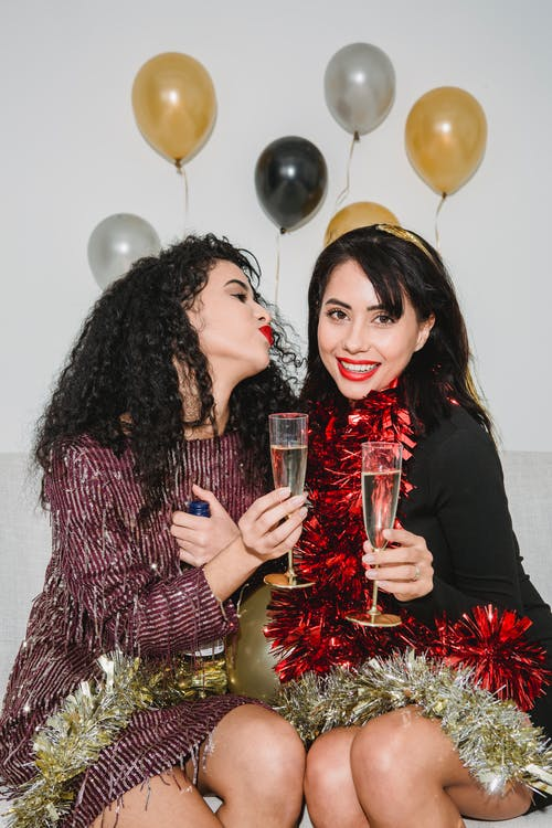 Happy young friends in festive dresses and sparkling bright tinsel entertaining at party among balloons