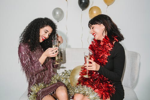 Positive women with glasses of champagne enjoying New Year
