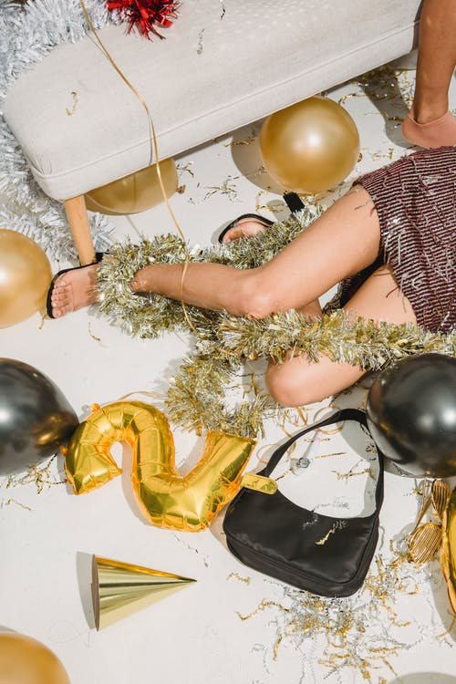 From above of crop anonymous drunk female in festive dress resting among balloons after party