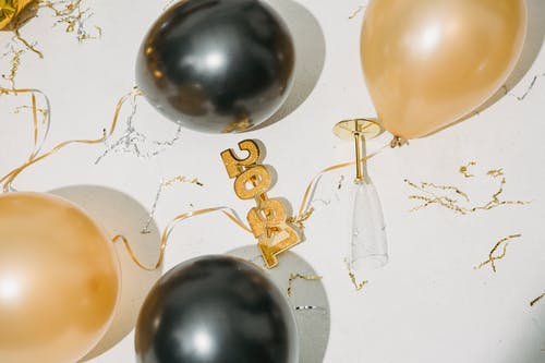 From above of Christmas decorations and empty glass placed on white surface after New Year celebration