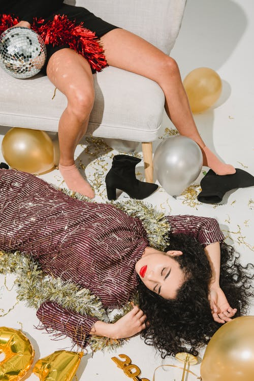 From above of drunk female in stylish dress sleeping on floor near friend lying on sofa in room with balloons and festive decorations after party