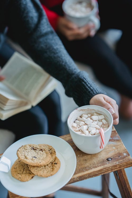 Female taking cup of cacao with marshmallows in cafe