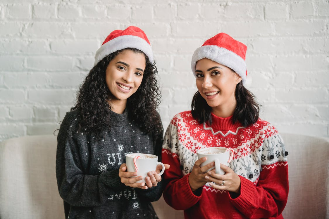 Multiethnic women sitting in room with cups of drink