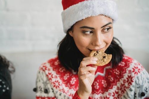 초콜릿을 먹는 빨간색과 흰색 산타 모자에있는 여자