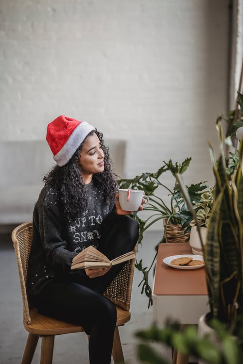 Young ethnic woman in sweater and Santa hat enjoying mug of hot drink with cookies while reading book on chair at home near plants and white wall