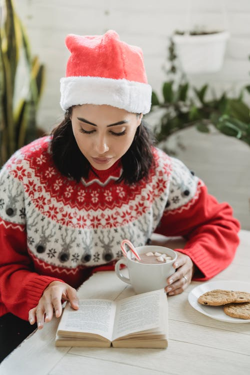 Young woman with hot cocoa and book