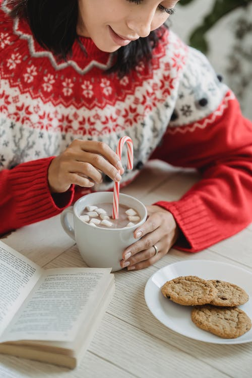 Person in Red Sweater Holding White Ceramic Mug With Pink Liquid