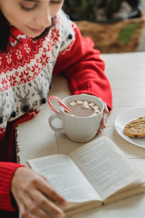 Person in Red and White Sweater Sitting Beside White Ceramic Mug on White Table