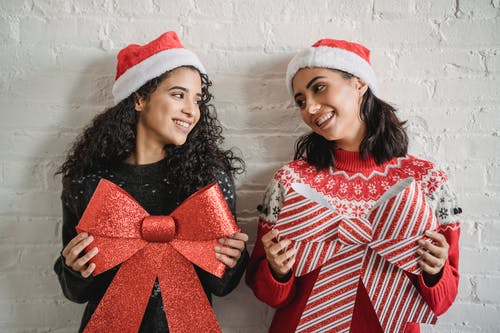 Happy young diverse women in Santa hats smiling and looking at each other while holding Christmas decoration