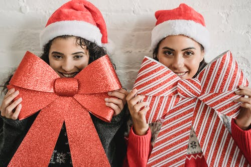 Cheerful women with Christmas decorative bows