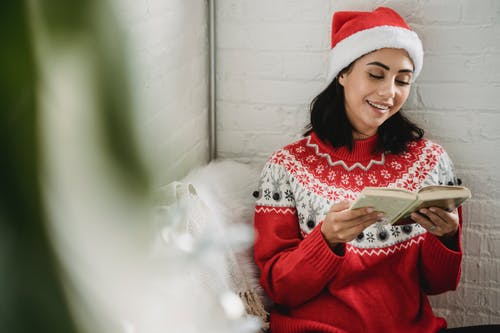 Young woman reading book on Christmas