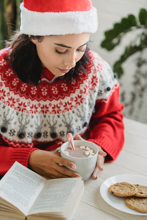 Young woman with hot beverage on Christmas