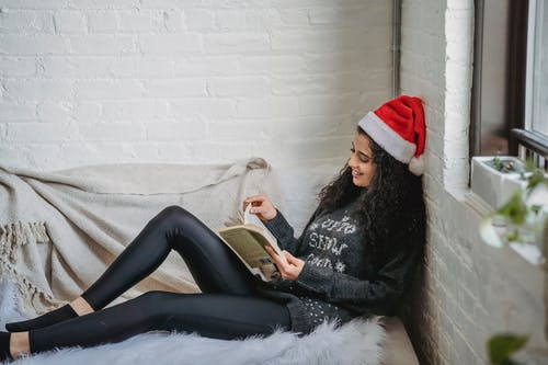 Side view of young female in casual clothes and Santa hat resting on sofa and reading book in modern living room on Christmas